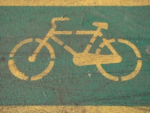 Image of a yellow bicycle symbol painted on a green background