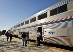 8075972-amtrak-conductor-and-passengers-on-a-sunny-platform.jpg